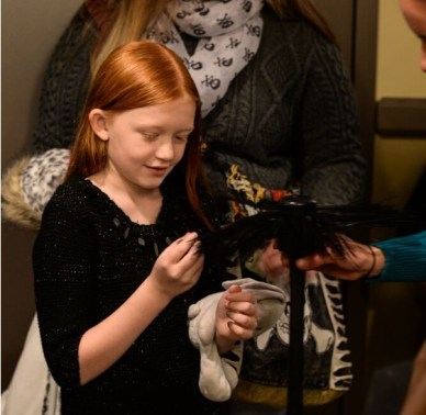 A young girl touches a prop