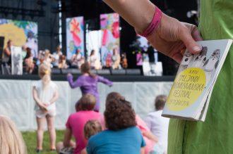 Kuvassa nainen seisomassa festivaalilavan edessä, kädessä festivaaliranneke ja -ohjelma