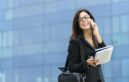 Woman walking and smiling on phone
