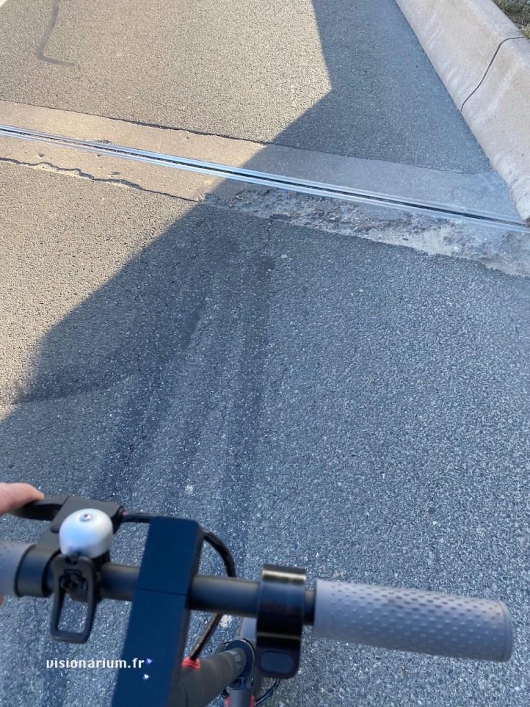 Grosse dégradation naturelle du goudron à la jonction entre la route et le pont. Sacrément dangereux en trottinette, avec ses roues de faible diamètre.