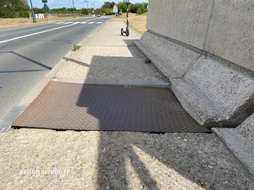 Plaque en métal, déformée, creusée, assurant la continuité piétonne au dessus d'un trou sur un pont.