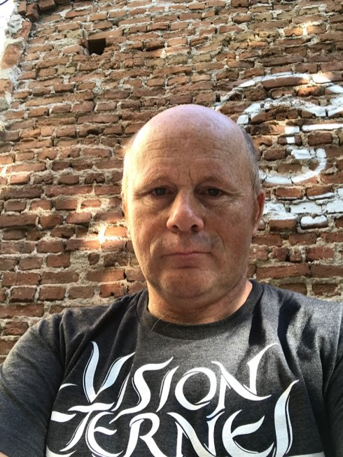 """Christophe Szpajdel wearing his Vision Éternel t-shirt outside the Young Freedom Cafe in Drama, Greece for the """"A Journey Into The Lost Homelands"""" exhibition."""