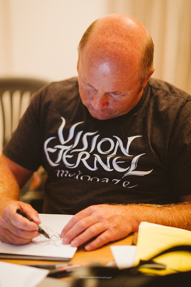 Christophe Szpajdel wearing his Vision Éternel t-shirt while designing logos in Drama, Greece.