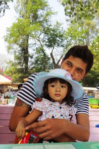 Young father and little girl in a white hat