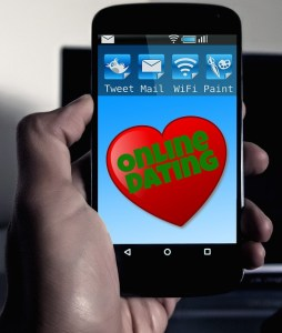 "Cell phone with image of heart and words ""Online Dating""."