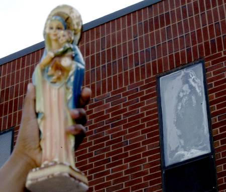 A girl holds up a statue of the Virgin Mary to compare it to an image in a Milton Hospital window that many believe resembles the Virgin Mary.