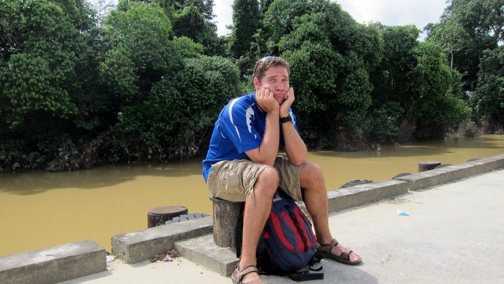 me sitting on the curb waiting for the bus. Borneo travel fail - a 5 hour bus ride to find out it's closed