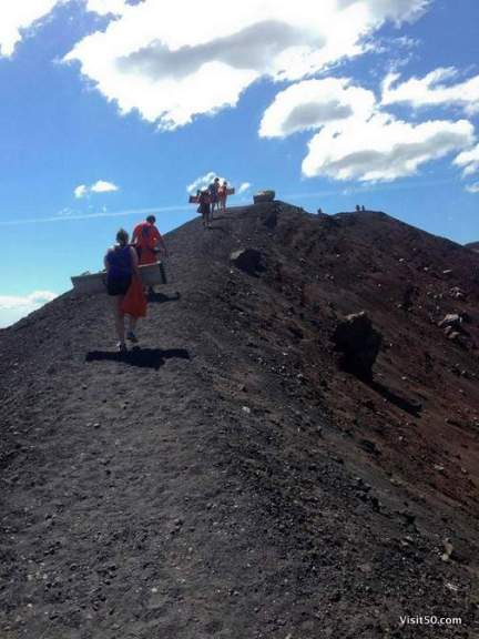 Climbing up a volcano cerro negro in Nicaragua. Lava rocks carrying plywood sleds and uniforms that look like prison suits