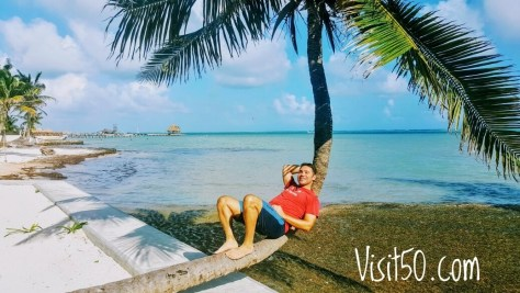 me in Belize under a palm tree. Choosing cheaper destinations helps you travel more.