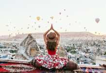 Woman on roof looking at hot air balloons in sky.
