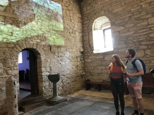 Woman and man watching the audiovisual presentation at St. Cronan's Church, Tuamgraney.
