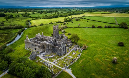 Quin Abbey as seen from above. It is surrounded by luscious green countryside.
