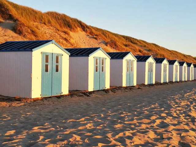 Little beach houses on one of the beaches of Texel, a wadden island in The Netherlands. In the background you will see dunes that have a red/orange colour because of the sunset.