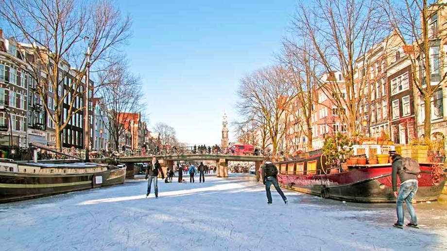 Ice on the canals in Amsterdam and people ice skating