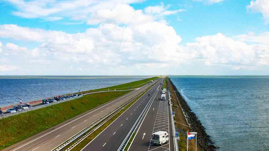 The longest dike in The Netherlands and Europe: Afsluitdijk, or closing dyke, with the Ijsselmeer on one side, a highway in the middle and the Wadden Sea Unesco Heritage Site on the left.