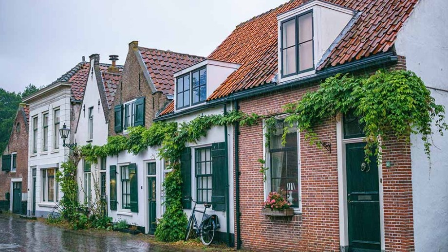 A view on old Dutch brick houses, covered in green during a rainy day in Brielle, The Netherlands