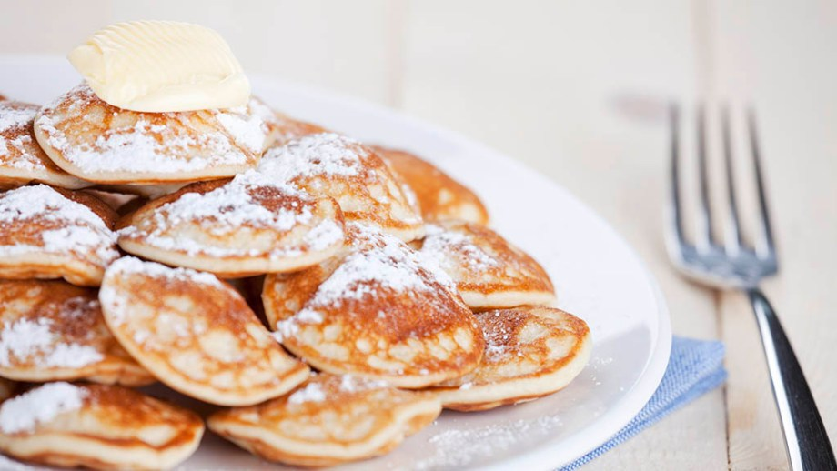 'Poffertjes': little Dutch pancakes with butter and powdered sugar. Shallow depth of field, focus on lump of butter.
