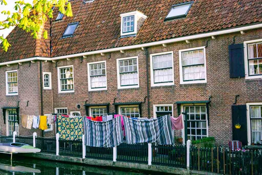 Photo of the clean laundry hanging to dry in the backyards of a row of historic Dutch houses in the village of Linschoten, The Netherlands