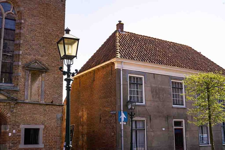 A photo of an old manor house and a brown brick church in The Netherlands