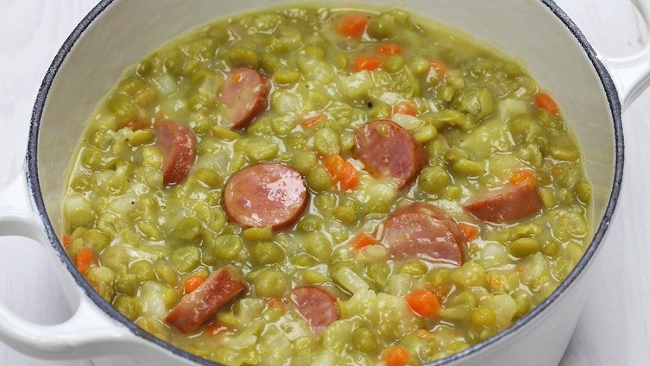 Dutch green pea soup from The Netherlands in a pot with sausage, carrots and spices