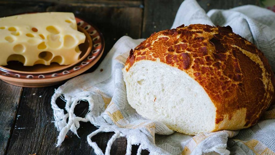 Tiger bread on a wooden table with cheese in a rustic style