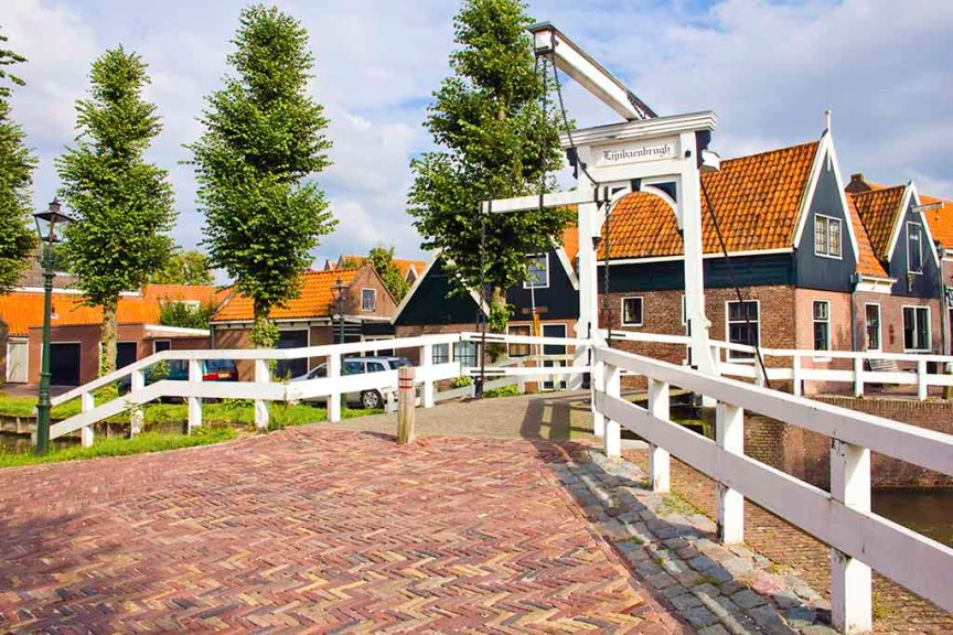 A view on an old bridge leading into the Dutch village of Monnickendam with traditional Dutch wooden and brick houses