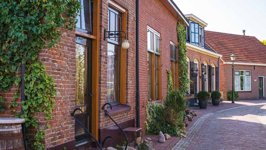 Brown brick Dutch houses with a bench and trees in front of them on a cobblestoned street in the village of Bredevoort