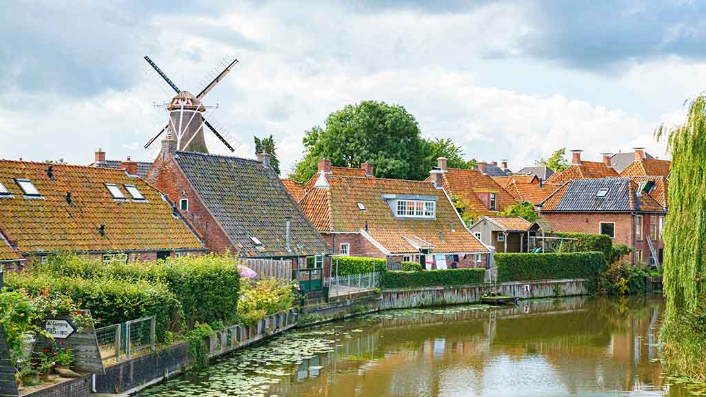 view on canal and historic dutch buildings in the town of Winsum, Groningen, The Netherlands