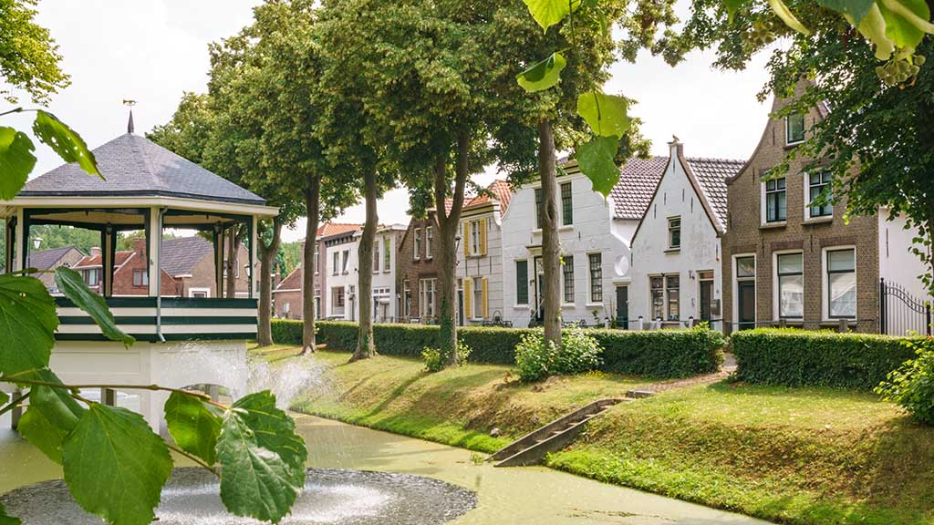 View on the main canal surrounded by dutch houses in Abbenbroek, The Netherlands