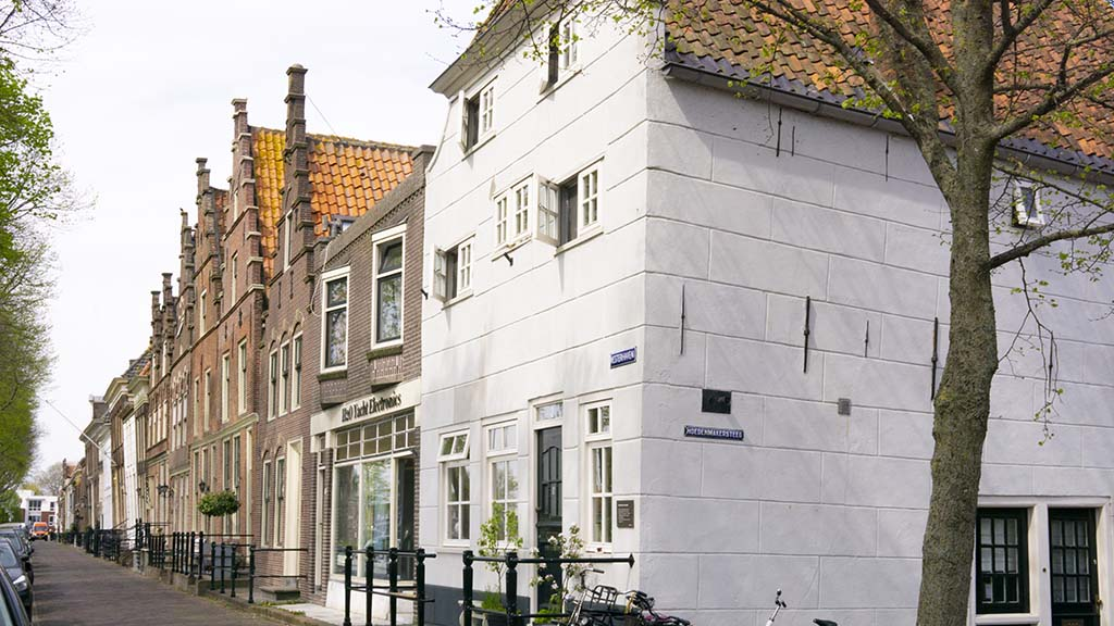 A view on canal houses and a cobblestoned street in the town of Medemblik, Noord- Holland, The Netherlands