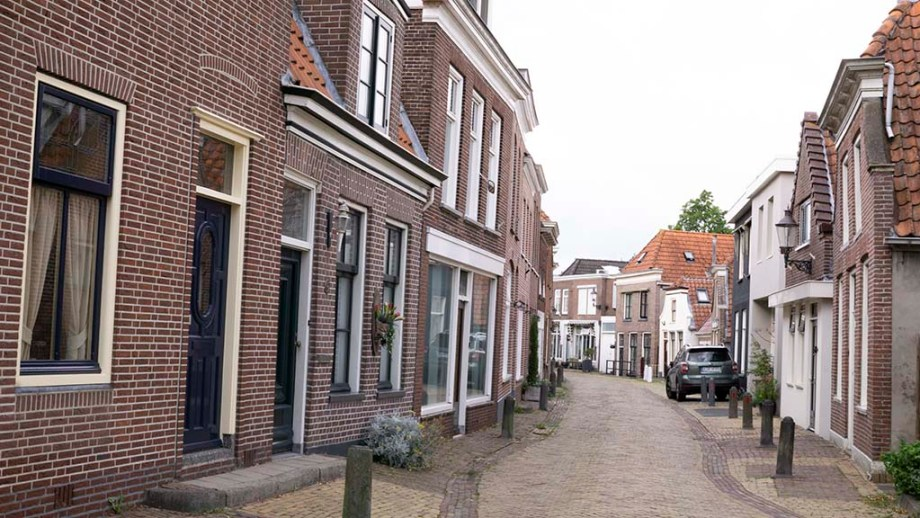 view on old Dutch brick buildings and historic cobblestoned street in Zwartsluis, Overijssel, The Netherlands