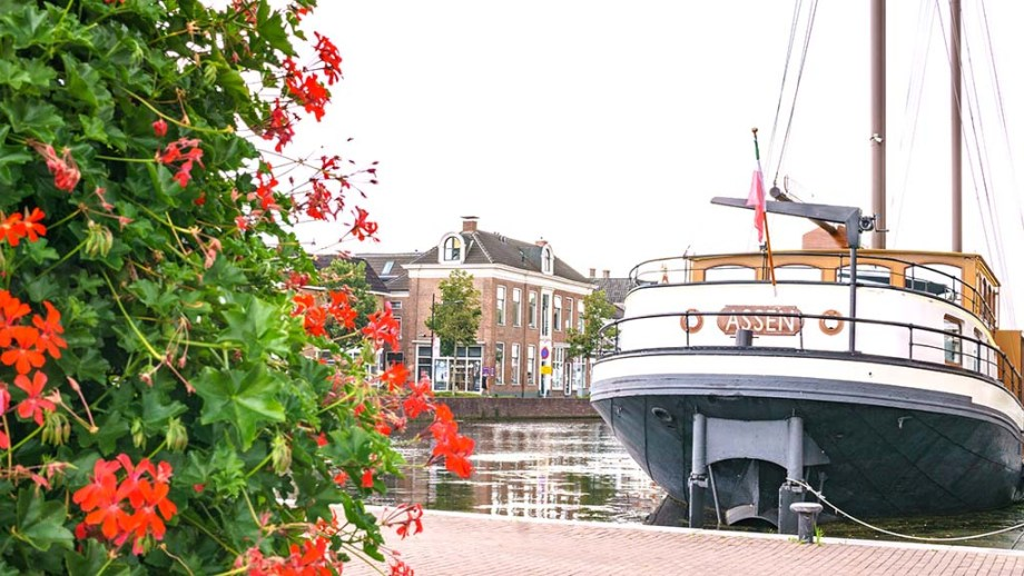 view on flowers and old buildings and a ship in the harbour of Assen, Drenthe, The Netherlands