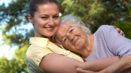 Grandaughter lovingly protecting grandmother from elder abuse