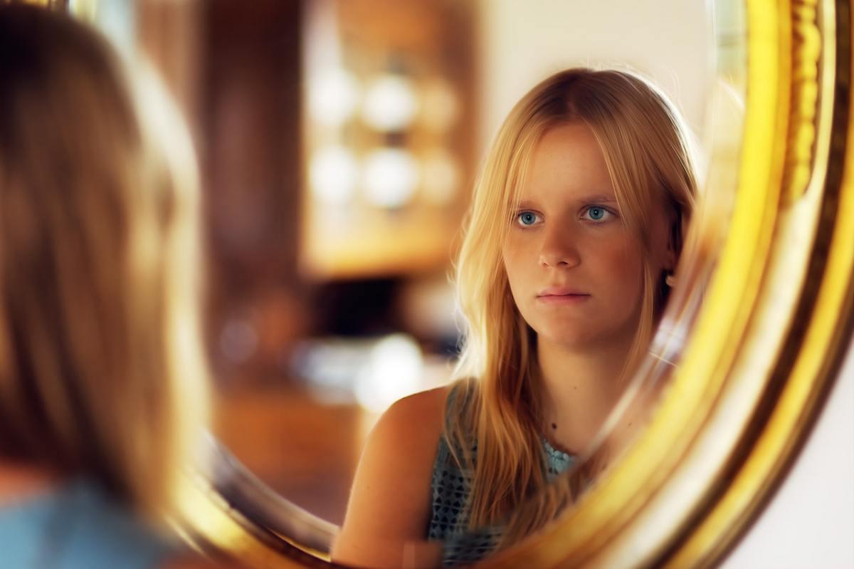 donna che si guarda allo specchio con tristezza