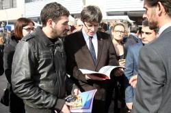 Puigdemont fullejant l'anuari Viu Molins de Rei 2015 // Marc Pidelaserra