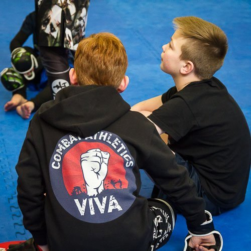 Max and Sam listening to instruction in the kids martial arts class