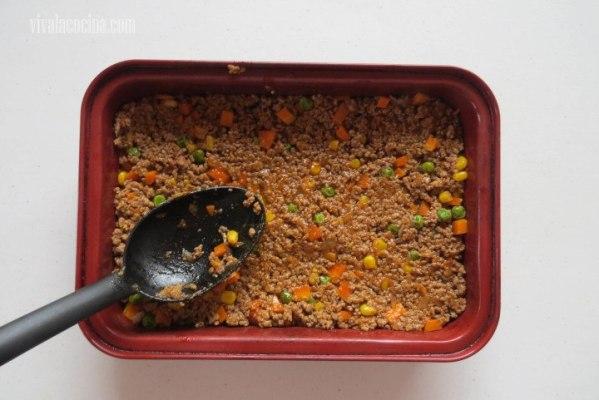 Colocar en un molde para horno que sea profundo y extender en una capa gruesa y uniforme la carne.