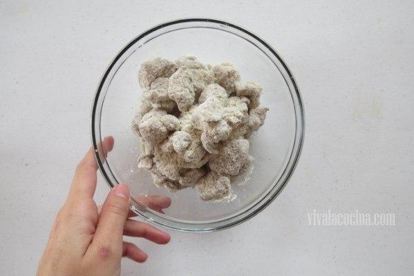 Colocar el pollo marinado en un bowl y agregar harina de maíz con un poco de pimienta molida