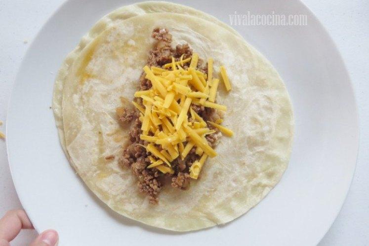 Añadir el guiso de carne molida al burrito y encima agregar un poco de queso chedda