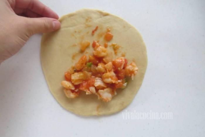 Extender la masa de las empanadas y colocar una cucharada de relleno.