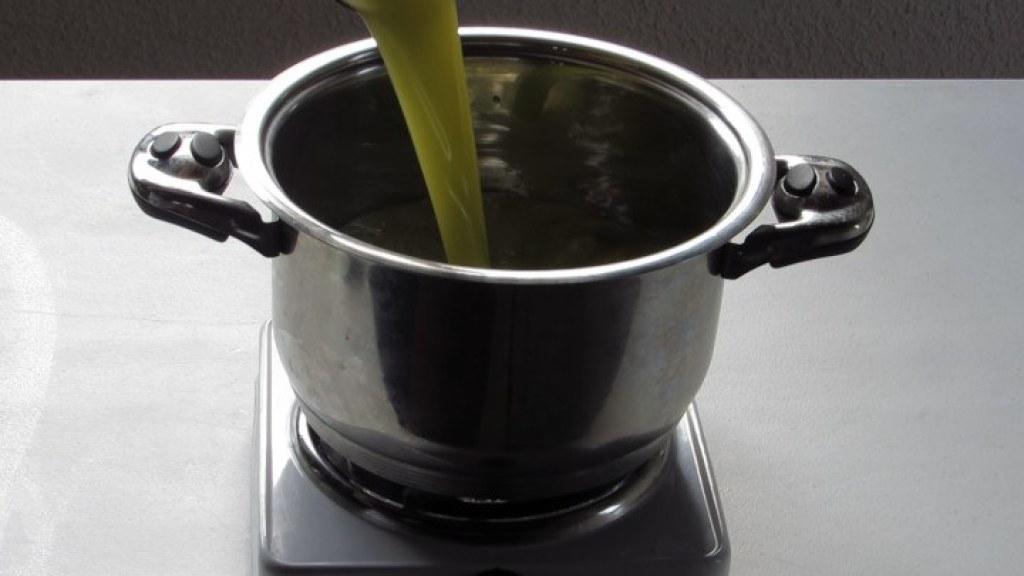 Vaciar el Jugo de manzana y pera en la cacerola para el ponche de manzanas