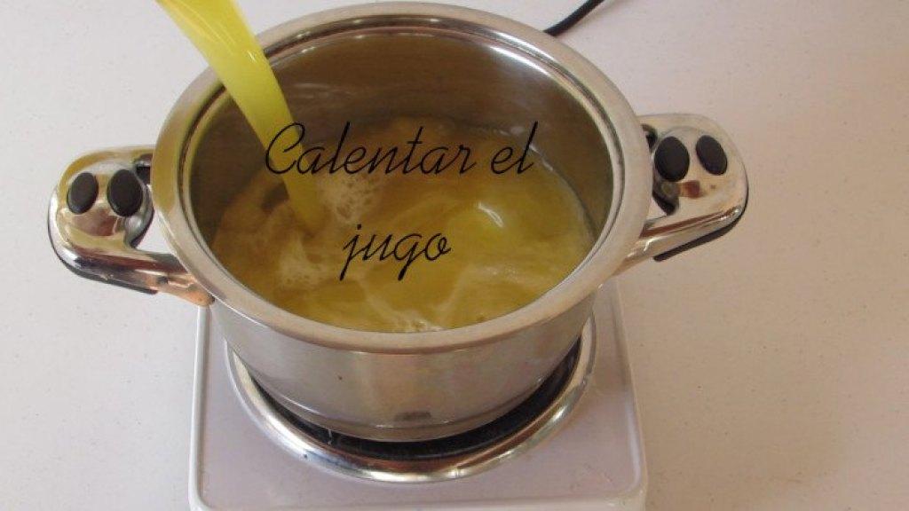 Calentar el jugo de piña para la gelatina de jugo de piña
