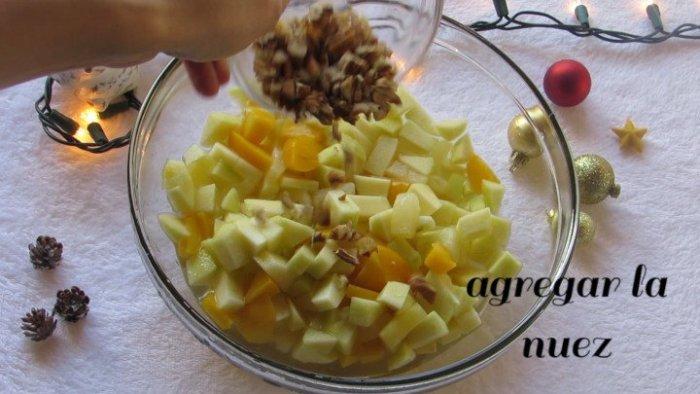 Mezclar nueces y fruta para preparar la Ensalada Navideña