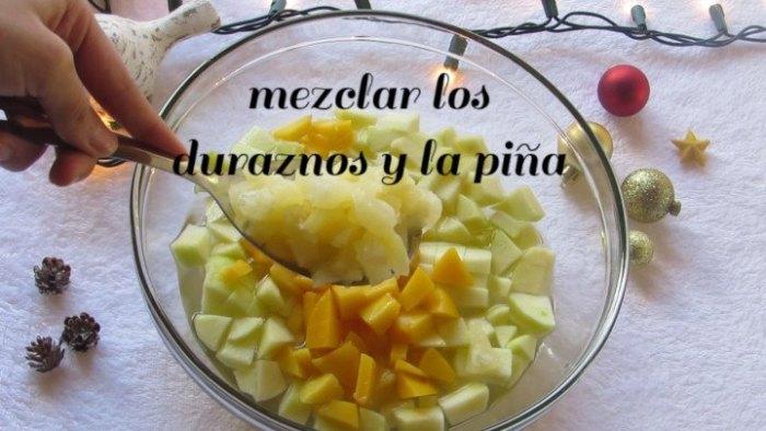 mezclar duraznos y piña para preparar la Ensalada Navideña
