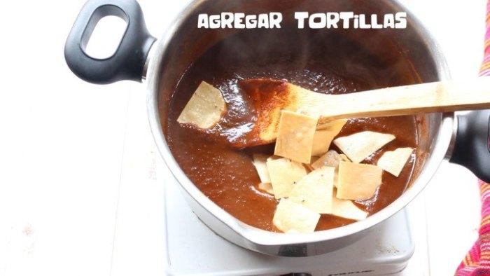 agregar tortillas a la salsa para hacer receta de chilaquiles