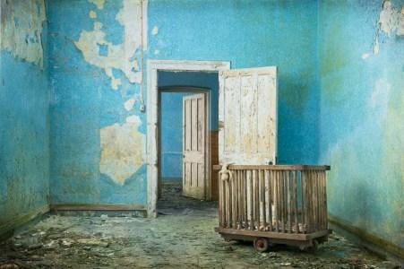 Blue room, vintage toys, doorway and doors, derelict Hellingly Asylum, West Sussex