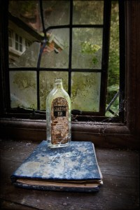 Empty bottle on a book by a window, derelict house