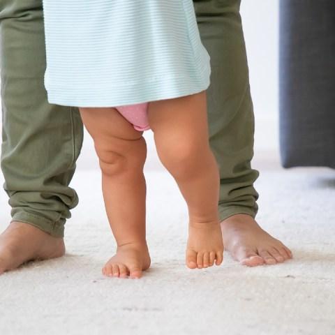bebé caminando sujetar de los brazos salud