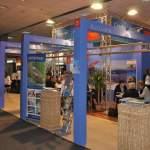CHRISTIAN TOUR - Stand expozitional personalizat cu structura si suprainaltare din grinda de aluminiu cu zabrele, placare cu PAL vopsit, pupitru info, scaune de bar, grafica de stand personalizata.