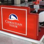 CHRISTIAN TOUR - Stand de prezentare in Afi Palace Cotroceni. Podea suprainaltata cu lumina in cant, totemuri iluminate, mobilier personalizat din PAL melaminat si sticla.